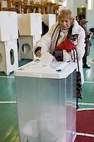 Moscow, Russia, 04/03/2012..A woman with her pet dog casts her ballot in a gymnasium as Russians vote in the Presidential election, which Prime Minister Vladimir Putin is expected to win in the first round.