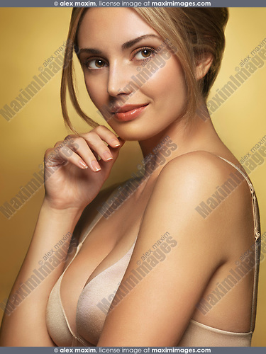 Beautiful smiling glamorous young woman with romantic daydreaming expression wearing a bra isolated on shiny golden background