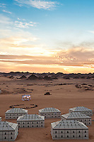 View over the black and white tents of the desert camp to the distant sand dunes and rocky outcrops of the Sahara Desert at sunrise