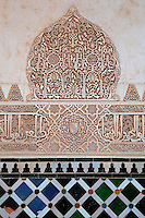 Detail of stucco work and tiles in the Court of the Myrtles or Patio de los Arrayanes, built in the 14th century under Yusuf I, in the Comares Palace, Alhambra, Granada, Andalusia, Southern Spain. The Alhambra was begun in the 11th century as a castle, and in the 13th and 14th centuries served as the royal palace of the Nasrid sultans. The huge complex contains the Alcazaba, Nasrid palaces, gardens and Generalife. Granada was listed as a UNESCO World Heritage Site in 1984. Picture by Manuel Cohen