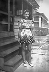 Teenager at summer beach cottages. 1940's black and white.