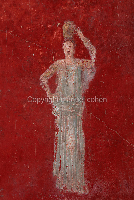 Fresco of a woman carrying a pot on her head, on a red background, in the cubiculum off the triclinium of the Casa del Sacerdos Amandus, or House of the Priest Amandus, Pompeii, Italy. The fresco is in the Third Style of Roman wall painting, 20–10 BC, characterised by an ornamental elegance in figurative and colourful decoration. Pompeii is a Roman town which was destroyed and buried under 4-6 m of volcanic ash in the eruption of Mount Vesuvius in 79 AD. Buildings and artefacts were preserved in the ash and have been excavated and restored. Pompeii is listed as a UNESCO World Heritage Site. Picture by Manuel Cohen