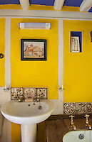 In the bathroom buttercup yellow walls and a deep blue ceiling create a stunning foil to the muted tones of the ornate Victorian ceramic tiles around the wash basin and bath