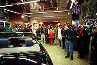 East Germans in a Mercedes showroom in West Berlin a few days after the opening of the Berlin Wall looking at high end sports cars the likes of which they had never seen before, except on television.