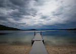 Idaho, North, Coolin, Indian Creek. A dock at Priest Lake State Park extends into Priest Lake under stormy skies.