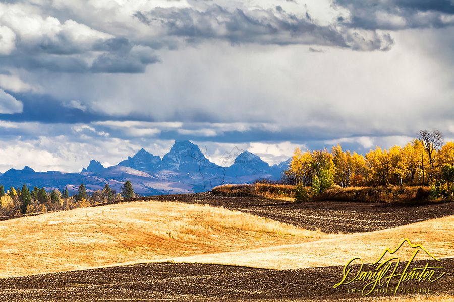 Autumn farmscape beneath the Grand Tetons of Teton Valley in Eastern Idaho. The rolling agrarian hills are a nice accent to the towering granite above.