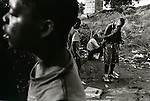 Former combatants gather to drink and smoke drugs in a rubbish dump, Luanda...Moses (smoking), 21 was a radio operator during the siege of Huambo and like.much of his generation.there, seeks only to forget and block out his experiences..Luanda, Angola, April 1998