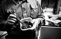 Roma 2000.Carcere di Regina Coeli  .Ufficio Pacchi, agente della polizia penitenziaria controlla il contenuto di un pacco in arrivo per i detenuti. Regina Coeli (Queen of Heaven) Prison..Agent penitentiary police control the content of a  Packages arriving for prisoners