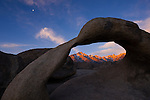 Mt. Whitney Mt. Muir and Mt. Irvine hit by the alpine glow of the rising sun as seen through the Mobius Arch in the Alabama Hills Recreation area in Lone Pine, California in the eastern Sierras along highway 395.