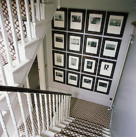 An ordered collection of black and white photographs creates a striking display on the staircase landing. The geometric patterned carpet gives the hall a monochromatic feel.