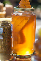 Jars of locally produced honey with honeycomb and bee pollen for sale at a farmers market.