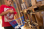 Daniel Garcia of Redwood City collects chicken eggs during afternoon chores at a Hidden Villa summer residential camp.