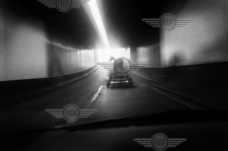 A fake horse being transported on a trailer pulled by a car in a road tunnel.