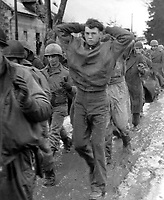 A lanky GI, with hands clasped behind his head, leads a file of American prisoners marching along a road somewhere on the western front.  Germans captured these American soldiers during the surprise enemy drive into Allied positions.  December 1944.  (Army)<br /> Exact Date Shot Unknown<br /> NARA FILE #:  111-SC-198240<br /> WAR &amp; CONFLICT BOOK #:  1071