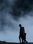 A man, woman and a child are silhouetted against a background of steam at a geyser basin in Yellowstone National Park.