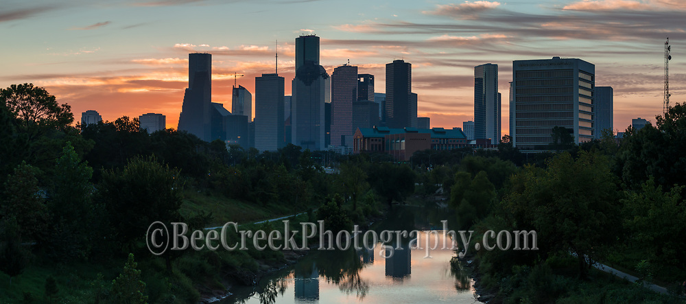 Houston skyline pano as sunrise was beginning to rise over the buffalo  bayou with the downtown high rise buildings in the background.  The water reflected the sky and skyline into the water along the bayou.