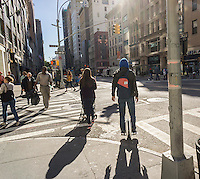 A unicyclist travels down Fifth Avenue in New York on his motorized segway-type unicycle onTuesday, October 6, 2015. (© Richard B. Levine)
