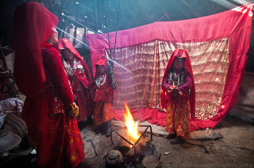 Ikhbal, 15, recently married, is kept hidden being a large red hanging cloth, inside a yurt, where she will stay for a few days. She will sleep there with her husband, be fed etc. Later, she will move to her husband's home. At the camp of Tash Seri (Mustafa Qol's camp). ..Trekking through the high altitude plateau of the Little Pamir mountains, where the Afghan Kyrgyz community live all year, on the borders of China, Tajikistan and Pakistan.