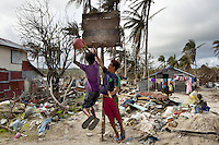 Philippines. Province Eastern Samar. Hernani. Bryan Samson (left, 16 years old) and his friend Donald Ayon (right, 12 years old), both players are jumping and playing basketball. They have rebuilt the board and hoop destroyed by typhoon Haiyan's winds and storm surge. 95 % of the town was destroyed by typhoon Haiyan. Typhoon Haiyan, known as Typhoon Yolanda in the Philippines, was an exceptionally powerful tropical cyclone that devastated the Philippines. Haiyan is also the strongest storm recorded at landfall in terms of wind speed. Typhoon Haiyan's casualties and destructions occured during a powerful storm surge, an offshore rise of water associated with a low pressure weather system. Storm surges are caused primarily by high winds pushing on the ocean's surface. The wind causes the water to pile up higher than the ordinary sea level. 26.11.13 © 2013 Didier Ruef