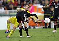 WASHINGTON, DC - OCTOBER 20, 2012:  Chris Pontius (13) of D.C United bent over by a tackle from Chris Birchall (8) of the Columbus Crew during an MLS match at RFK Stadium in Washington D.C. on October 20. D.C United won 3-2.