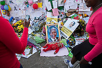 A baby lies in front of a picture of Nelson Mandela outside the Medic-Clinic Heart hospital where the former president is being treated, in Pretoria, South Africa.