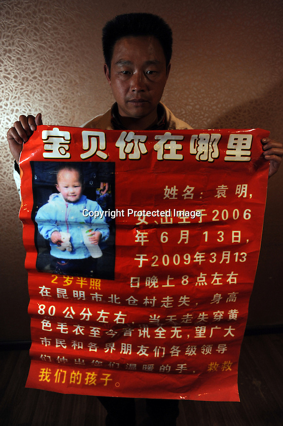 Yuan Yingshu, 36, holds a missing person advert for his two and half year old missing daughter Yuan Ming, who went missing on March 13, 2009. Kunming is one of China's hot-spots for child abductions in China.