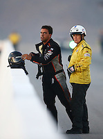 Oct 31, 2015; Las Vegas, NV, USA; NHRA funny car driver Brandon Welch is tended to by members of the safety safari after an engine fire during qualifying for the Toyota Nationals at The Strip at Las Vegas Motor Speedway. Mandatory Credit: Mark J. Rebilas-USA TODAY Sports