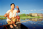 An Intha woman takes a break from rowing her boat and makes pendants out of Lotus flowers on Lake Inle in Shan State, Myanmar.