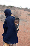 MATHAHALIBAH, KENYA - JULY 4: Mohammedek Siyad, 21 months old, is carried home by his grandmother after visiting a Save the Children outreach site in the location on July 4, 2011 in Mathahalibah, Kenya. The team examined about thirty children, among them several severely malnourished. Mohammedek's grandmother Habiba Sahal came with him to the outreach site to receive some food and medicine. His mother left three months ago with their remaining livestock. Forced away due to the sever drought in the area. She is expected back when rain falls again. Mohammedek is now being cared by his grandmother. Two successive poor rains, entrenched poverty and lack of investment in affected areas have pushed millions of people into a fight for survival in the Horn of Africa. This the driest this area had been since 60 years. This is the driest this area have been since sixty years. (Photo by Per-Anders Pettersson)