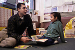 Berkeley CA Latino college student, student teacher,  chatting with first grader about book in bilingual Spanish-english class