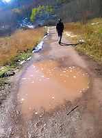 Love. Heart made of mud on country path, with person man walking ahead, in winter with snow. Amazing unexpected romantic love in puddle, divine intervention