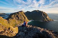 Hiker on the summit of Ryten with Kvalvika beach in background, Moskenesøy, Lofoten Islands, Norway
