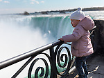 Two year old girl standing at a barrier and looking at Niagara Falls. Ontario, Canada.