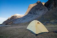 Tent pitched below Helvetestind mountain peak at Bunes beach, Moskenesøy, Lofoten Islands, Norway