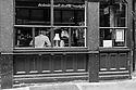 London, UK. 04.04.2015. People through a pub window, East London. Photograph © Jane Hobson.