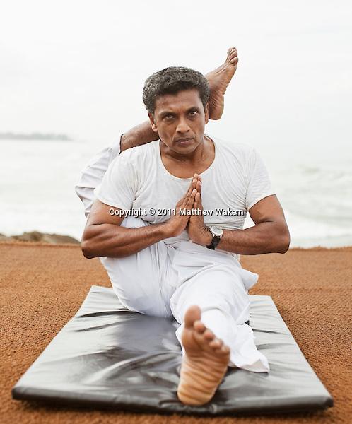 Sri Lankan yoga master practices yoga by the beach at Saman Villas, Aturuwella, Bentota, Sri Lanka; shown here is one foot to head pose (or eka pada sirasana).