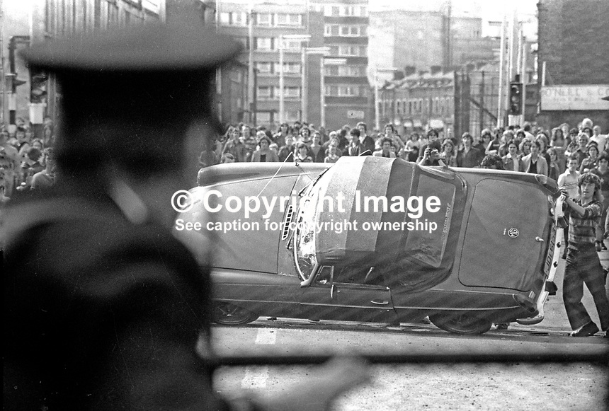 The Silver Jubilee visit of Queen Elizabeth II to N Ireland on 10th &amp; 11th August 1977 sparked serious rioting in Belfast as those opposed to the visit tried to reach the city centre. Policeman watches as rioters overturn a sports car.  197708100074g<br />