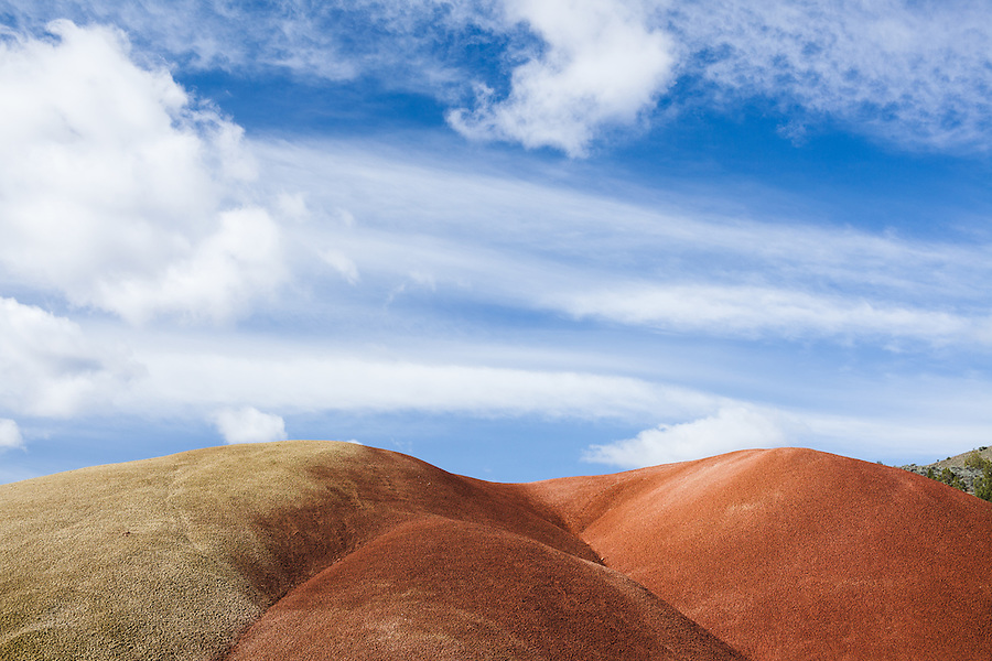 A curvy red and yellow colored hill is seen with broken while clouds in a blue sky at the Painted Hills section of the John Day Fossil Beds National Monument in Wheeler County, Oregon.