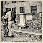 Two people looking at a gravestone in the Granary Burying Ground in Boston, MA