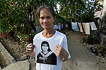 Josefina Marcos holds a portrait of her daughter, Griselda Ramirez, at her home in Pangasinan in the Philippines. Griselda left for Hong Kong to work as a domestic servant in 2007, in order to raise money for an operation on her brother. Yet she was mistreated and escaped from her employer and has been assisted by the Bethune House Migrant Women's Shelter.