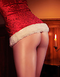 Closeup of woman in sexy red Christmas costume revealing her sensual buttocks and thighs in romantic indoor settings