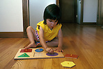 Berkeley CA Girl, two and half-years-old doing simple shape puzzle at home  MR