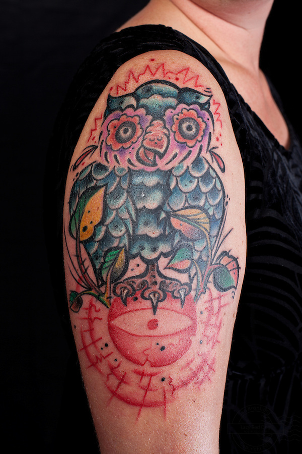 Danish woman with owl tattooed on right shoulder and the third eye on lower right arm.<br /> From the Kolding Tattoo Convention.