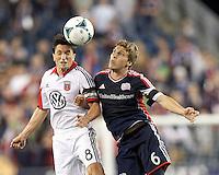 D.C. United midfielder John Thorrington (8) and New England Revolution midfielder Scott Caldwell (6) battle for head ball.  In a Major League Soccer (MLS) match, the New England Revolution (blue) defeated D.C. United (white), 2-1, at Gillette Stadium on September 21, 2013.