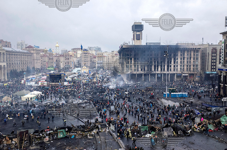 A view of Maidan Nezalezhnosti (Independence Square), renamed EuroMaidan by protesters since November 2013, littered with detritus and signs of fires, in central Kiev. Protests against the government of President Viktor Yanukovych were sparked on 21 November 2014 by the Ukrainian government's decision to suspend preparations for the signing of an association agreement with the European Union that would have increased trade with the EU. Some believe that the U-turn came about as a result of pressure from President Putin of Russia who wants Ukraine to join a customs union with itself, Kazakhstan and Belarus. Russia offered 15 billion dollars of soft loans and reduced price gas to Ukraine at the same time as discussions with the EU were taking place. After weeks of protests and a number of deaths, Prime Minister Mykola Azarov and the entire cabinet resigned. Protesters are holding out, however, for President Yanukovych to resign and continue to occupy public buildings and squares to put pressure on the president. On 18 February, after Yanukovych's party scuppered a move to change the constitution to reduce the powers of the president, renewed fighting between protesters and police broke out and had cost the lives of around 80 people by Friday 21st February.