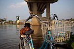"Sao, 49, washes his bicycle in the Hau Giang River, a tributary of the Mekong River, in Chau Doc, in the An Giang Province, Vietnam. When the Mekong River reaches Vietnam it splits into two smaller riveres. The ""Tien Giang"", which means ""upper river"" and the ""Hau Giang"", which means ""lower river"". Photo taken on Monday, December 7, 2009. Kevin German / Luceo Images"