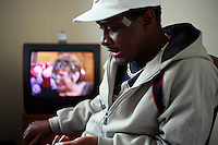"""34 year old Alain sits at a friends house in Walthamstow, London. After fleeing DR Congo and claiming asylum in the UK in 2002 he spent months destitute. His work as a TV journalist led to his arrest and torture by government soldiers in DR Congo, and only after paying a huge bribe was he able to escape and flee the country. If he returns he believes he will be killed. His asylum claim was refused, and unnable to work or support himself, he began sleeping rough in the Elephant and Castle area of London. He is completely destitute and struggles to survive, depending on a friend who is also a refused asylum seeker but who has support from section 4 of the Immigration and Asylum Act 1999 (no choice of accommodation and GBP 35 of supermarket vouchers a week). Two years ago Alain was the victim of a racist attack, when a white man blinded him in one eye with a piece of broken glass. """"As asylum seekers we have been punished twice - once back home and once here. In Kinshasa I was tortured physically and here I'm tortured mentally. I've transferred from one prison to another."""" Alain is one of an estimated 300,000 rejected asylum seekers living in the UK. .."""