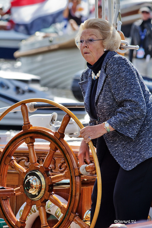 Nederland,Offingawier,11-08-2010 Koningin Beatrix aan het roer van het koninklijke jacht De Groene Draeck varend op het Snekermeer. De koningin bezoekt het zeil evenement De Sneekweek tijdens Hardzeildag. Het evenement wordt dit jaar voor de 75e keer gehouden. Dutch Queen Beatrix at the rudder of her traditional yacht The Groene Draeck during a sailing event called the Sneekweek. FOTO: Gerard Til / Hollandse Hoogte