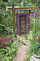 An exotic colored gate creates an air of mystery at the  entry of the backyard in Dan Johnson's Denver garden.