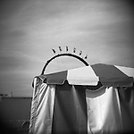 Monochrome Holga carnival image of striped tent with ride in background